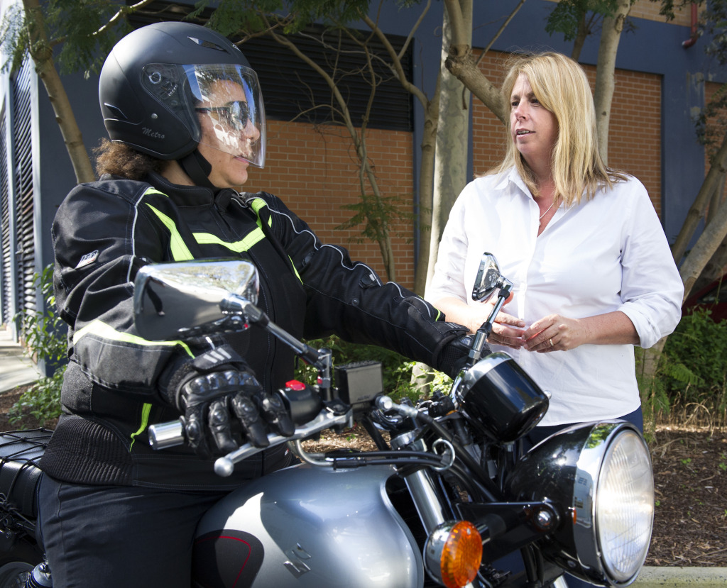 Dr Julie Brown discusses road safety with a motorcyclist.